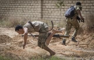 المحاربون الموالون لحكومة الوفاق الوطني المعترف بها دولياً يركضون للاحتماء خلال المصادمات مع القوات الموالية لخليفة حفتر جنوب ضاحية عين زارة في العاصمة طرابلس ، في 25 أبريل/نيسان 2019.
