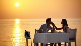 زوجان يستمتعان بعشاء رومانتيكي على الشاطئ