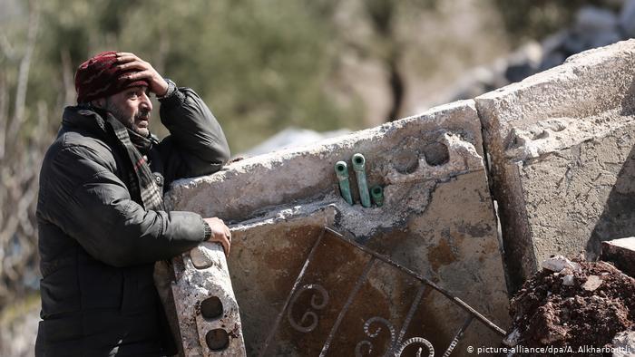 صورة من الأرشيف: رجل سوري يقف أمام بناية محطمة بعد قصف جوي روسي