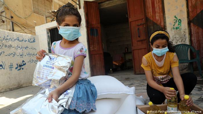 فتيات في غزة يتلقين المساعدات الغذائية من الاونروا